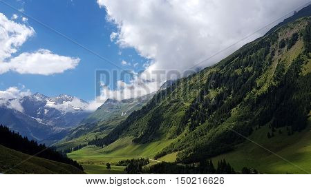 Amazing view of austrian alps with green valley and summer clouds.