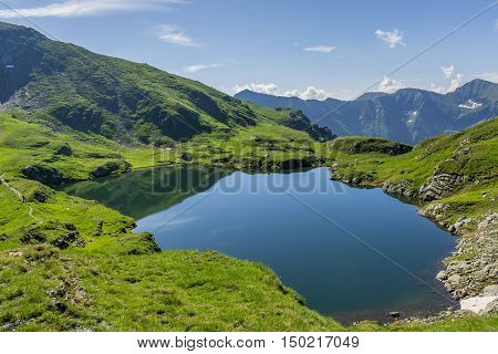 Mountain lake with crystal clear water. Landscape from Capra Lake in Romania and Fagaras mountains in the summer.