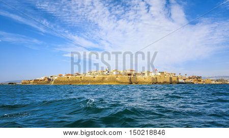 View from the sea to the ancient fortress city of Acre in Israel against the backdrop of a colorful sky.