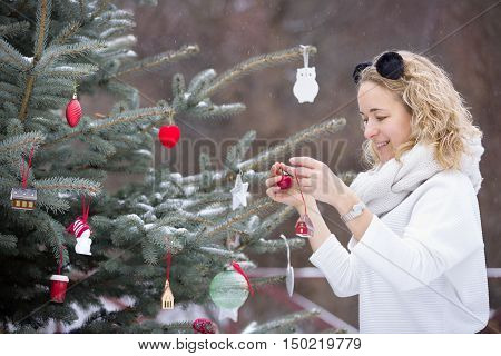 Portrait of young beautiful woman decorating Christmas tree outdoors. New Year celebration. Holidays concept