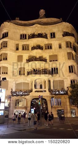 Barcelona, Spain - June 24, 2016: Illuminated facade of Casa Mila at night. Tourists take pictures.