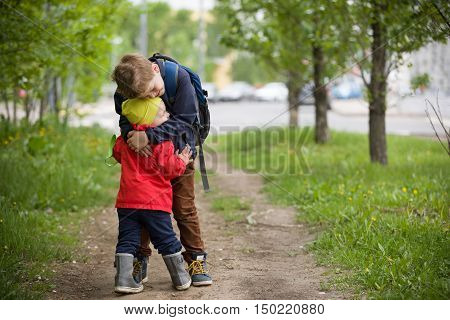 Two little brothers hugging each other when meeting in the park. Cute kid boy meets his little toddler sibling and hugs him. Happy children walking on the road. Lifestyle and family concept