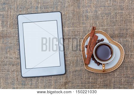 Morning coffee with cinnamon and ebook. Top view