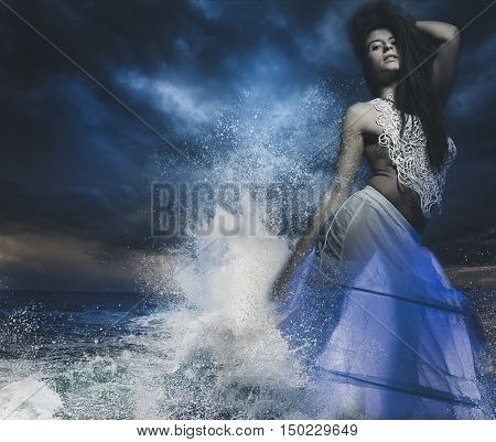 brunette woman with braided hair by the sea with the waves crashing