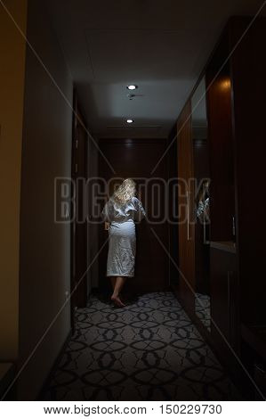 Women with Bathrobe looking through the Peephole in Hotel Room