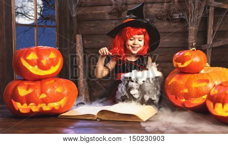 Halloween. child girl witch preparing a potion in the cauldron with pumpkins