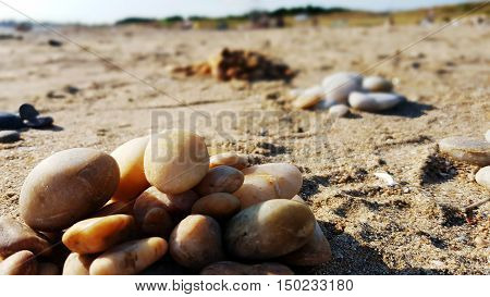 Piles of round stones on the sandy beach.