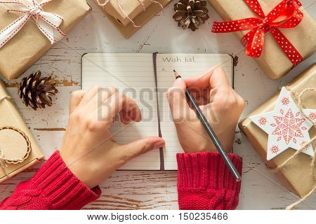 Making list of presents on wood background, copy space