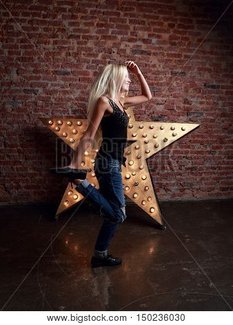 Happy Trendy Teen Girl Dancing And Jumping On Yellow Star And Brick Wall Background