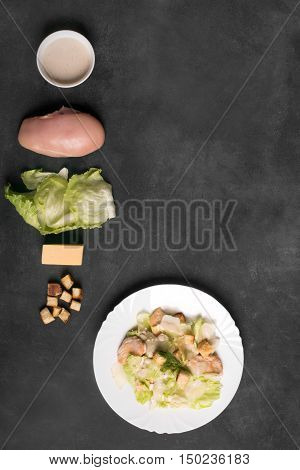 Classical Caesar salad with sliced chicken meat, fresh salad leaves, croutons and sauce in white round plate. Copy space for your text