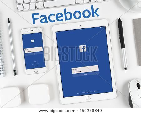 Moscow, Russia - October 04, 2016: Facebook inscription printed on background and Facebook application on the iPhone and iPad display. Facebook is largest social network in the world founded in 2004.