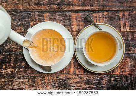 Pouring two white china cups of tea on wooden table