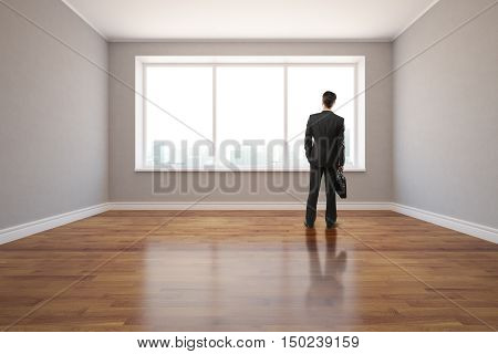 Back view of young businessman standing in unfurnished interior with shiny wooden floor grey walls and window with city view. 3D Rendering