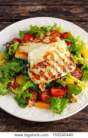 Grilled Halloumi Cheese salad witch orange, tomatoes and lettuce. healthy food.