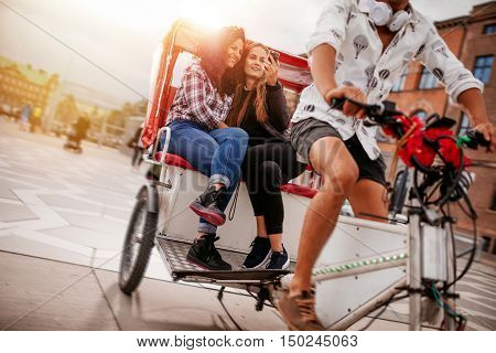 Shot of teenage girls taking selfie on tricycle ride. Young female friends riding on tricycle bike and taking self portrait.