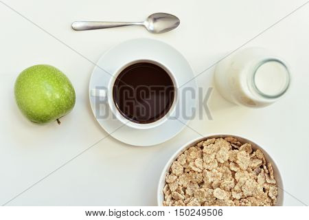 high-angle shot of a white table set for breakfast with a green apple, a cup of coffee and a bowl with cereals