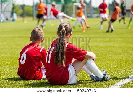 Children soccer players playing game. Young girl and boy soccer players sitting together on grass football field