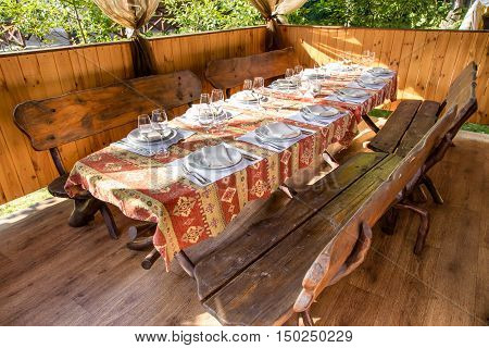 Table served with dishes close up in a wooden gazebo. On the table are forks knives plates glasses