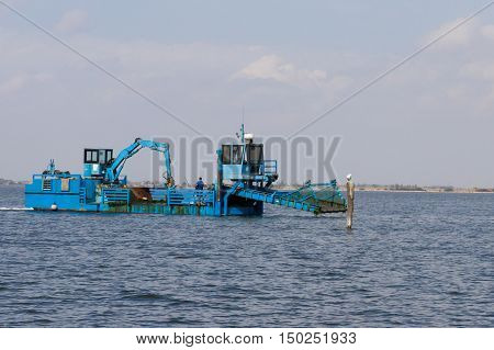 Close up of a blue dredger working on italian Po river lagoon. Industrial vehicle