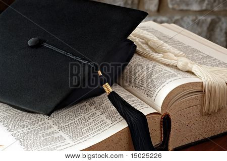 Graduation cap with tassel and honor cords lying on open dictionary.  Defined word in strongest focus is