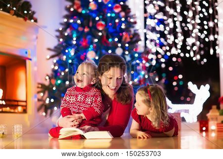 Family on Christmas eve at fireplace. Mother and little kids opening Xmas presents. Children with gift boxes. Living room with traditional fire place and decorated tree. Cozy winter evening at home.