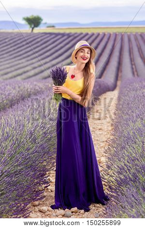 Young pretty woman in the long violet skirt standing with lavender bouquet on the lavender field in Provence in France