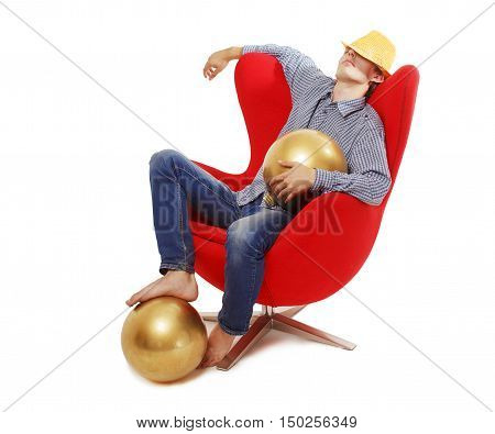 guy resting in a chair after the New Year's party. man sitting in a red armchair with Christmas balls. the concept of gilded youth. isolated on white background