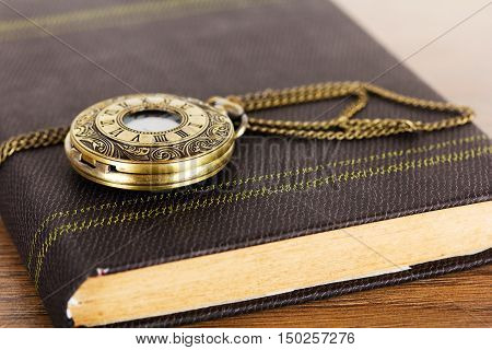 Pocket Watch And Book Against A Rustic Background