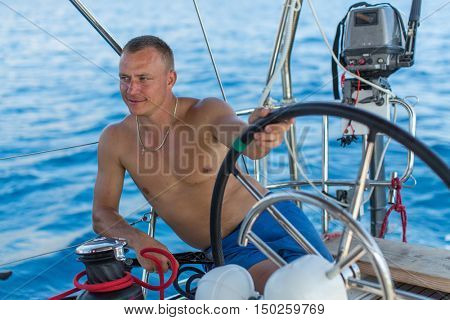 Man skipper relaxed runs his sailing yaht boat.