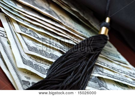 Higher education conceptual image with graduation cap and tassel on american currency.  Macro with extremely shallow dof.