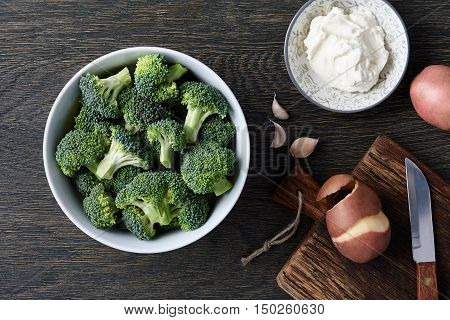 A bowl with fresh broccoli, cloves of garlic, potatoes and cream cheese on dark wooden background. Brocoli soup ingredients.