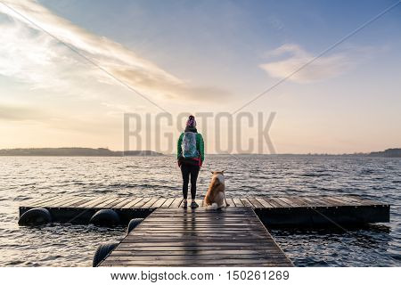 Woman with dog enjoy sunrise and lake relaxing on bridge. Hiker or tourist looking at beautiful morning view with dog friend inspirational landscape on beach. Peaceful people and serene concept.