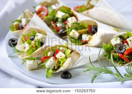 Mini tortillas stuffed with Greek farmers salad with feta cheese and olives, served in white paper bags