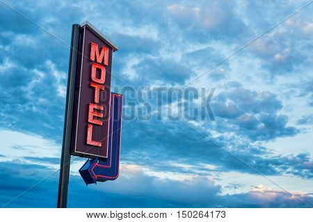 Red motel neon sign over a sunset cloudy sky