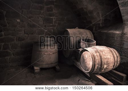 Old wine cellar and wooden barrels - Vintage image with the interior of a stone wine cellar and aged wooden barrels in low light. Perfect background or frame for a country life concept or medieval way of making wine.