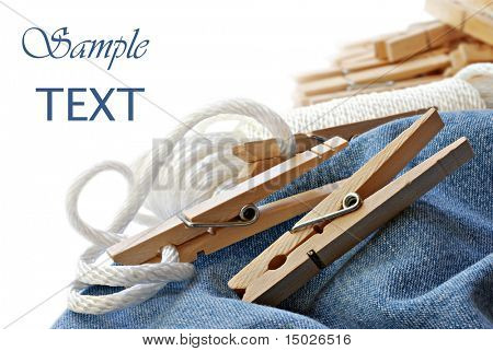 Wooden clothespins with coiled clothesline on freshly laundered denim fabric.  Macro with shallow dof.  Copy space included.