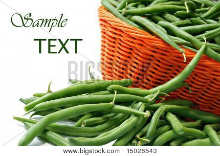 Fresh green beans in orange wicker basket on white background with copy space.  Macro with shallow dof.