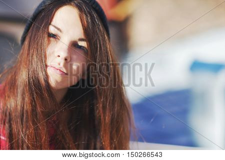 Nice long-haired girl with blue eyes on a clear Sunny day the wind had tossed her hair close up on blurred background.