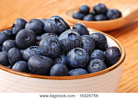 Bowl of fresh blueberries with wooden spoonful of berries in background.