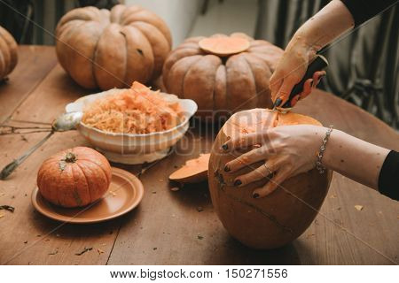 woman hands curving pumpkin preparing for Halloween