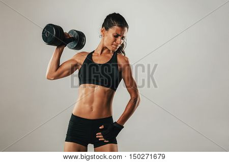 Fit Young Woman Holding A Dumbbell Aloft