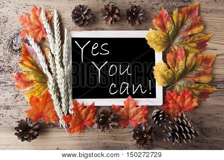 Blackboard With Autumn Or Fall Decoration. Greeting Card For Seasons Greetings. Colorful Leaves, Fir Cone And Barley On Aged Wooden Background. English Quote Yes You Can