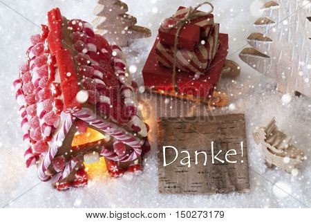 Label With German Text Danke Means Thank You. Gingerbread House On Snow With Christmas Decoration Like Trees And Moose. Sleigh With Christmas Gifts Or Presents And Snowflakes.