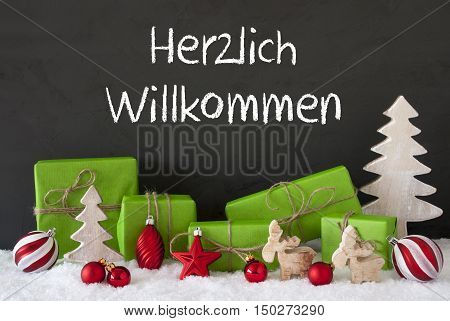 German Text Herzlich Willkommen Means Welcome. Green Gifts Or Presents With Christmas Decoration Like Tree, Moose Or Red Christmas Tree Ball. Black Cement Wall As Background With Snow.