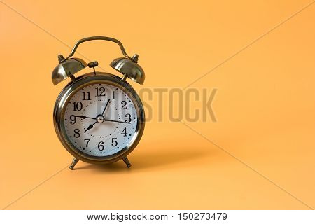 alarm clock on orange background and copy space and write space for write text or message / time concept