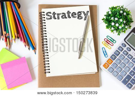 strategy text message on white paper and office supplies, pen, paper note, on white desk , copy space / business concept / view from above, top view