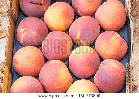 Top view of delicious red yellow peaches in a cardboard box.