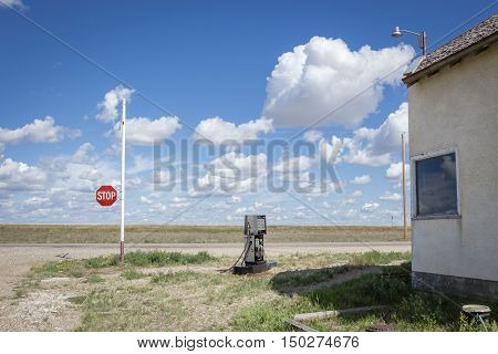 horizontal image of an old broken gas pump station sitting next to an old closed store with a stop sign at the end of the road under a beautiful blue sky with clouds in the summer time.