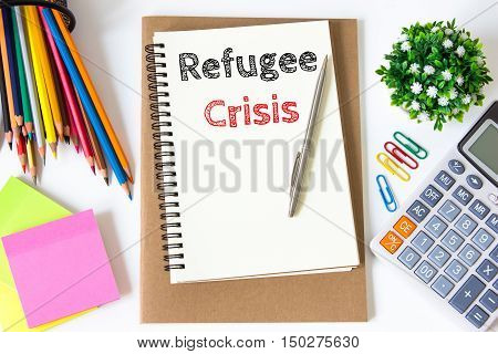 refugee crisis text message on white paper and office supplies, pen, paper note, on white desk , copy space / business concept / view from above, top view