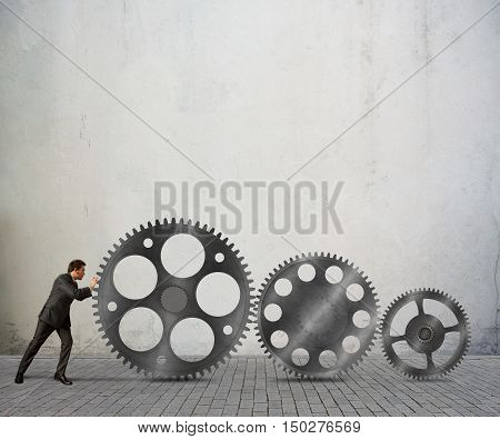 Businessman pushes a system mechanism of gears